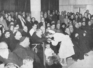 Padre Pio at the Home for the Relief of Suffering attends a program in the auditorium. A staff nurse greets Padre Pio and kisses his hand.
