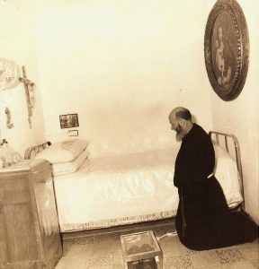 Brother Modestino kneels in prayer in Padre Pio's cell at the monastery of Our Lady of Grace.